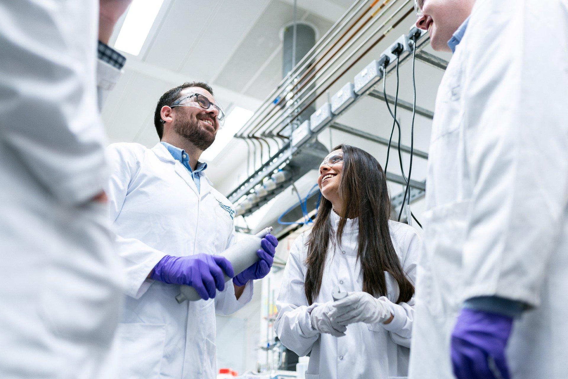 Unterhaltungs eines Forschungsteams von 4 Personen im Kreis stehend mit Handschuhen, Kitteln und Sicherheitsbrillen